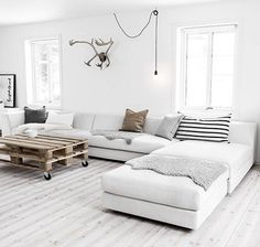 witte vloer, bank en muur, salontafel van steigerhout en een leuke manier om een lamp op te hangen
