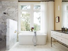 In the master bathroom, a luxurious soaking tub with a floor-mounted faucet is positioned in front of the window. Soft, breezy curtains provide privacy when the standalone tub is in use.