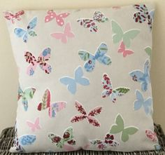 These cream cushions are handmade with a pretty fabric with pale pink, pale blue, light green and multicoloured butterflies with red accents.  The cushions are made from 100% cotton with an envelope back so the cushion cover can be removed easily. Dimensions: 16 inches wide x 16 inches tall (40.5cm x 40.5cm)  Each cushion is handmade so the pattern placement may differ slightly from the attached photographs and please note that the cushion pad can be included as an extra variation…