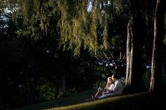 casal de noivos sentados na grama e encostados na arvore e olhando o por do sol em curitiba
