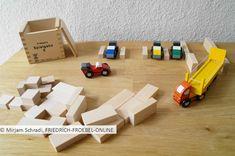 Beim Bauen von einem Parkplatz für kleine Holzautos- Spielidee für Kinder mit Fröbelbausteinen