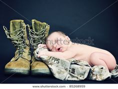 Military baby laying on military blouse/trousers with combat boots as a pillow!
