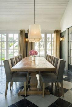 A reclaimed-wood dining table with a chunky base from Mas Infinito provides a rustic counterpoint to the custom winged chairs upholstered in stonewashed grey canvas with bronze nailhead trim | archdigest.com