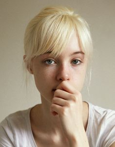 blue eyes - bangs - blonde - hair tied up - white shirt - hand over mouth - female - shoulder up portrait