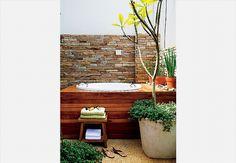Aqui, a banheira de hidromassagem ganhou deque de grápia. A parede ganhou canjiquinha de pedras mineiras