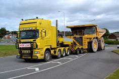 Scania pulling very low beam trailer moving the Komatsu off road dump...