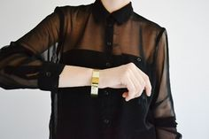 Clean sophistication-- sheer black blouse with simple gold bangle