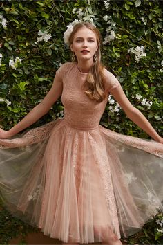 Emelia Dress from BHLDN With a frothed fit-and-flare silhouette enveloped in a layer of dreamy tulle and a sheer, open back, this blush dress from Tadashi Shoji is cheerful and refined at once.