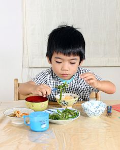 """Occasionally, their mother, Fumi, lets them eat cold cereal and doughnuts, but she wants her children to grow up knowing what it means to eat Japanese. Here, Koki eats green peppers stir-fried with tiny dried fish, soy sauce and sesame seeds; raw egg mixed with soy sauce and poured over hot rice; kinpira, a dish of lotus and burdock roots and carrots sautéed with sesame-seed oil, soy sauce and a sweet rice wine called mirin; miso soup; grapes; sliced Asian pear; and milk."""