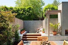 Kleiner Garten mit Holzzaun und Betonmauer von den Nachbarn abgeschirmt