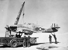 Personnel of No. 53 Repair and Salvage Unit use a Coles Crane to haul the fuselage of damaged Hawker Hurricane Mark IIB, BD930 'R', of No. 73 Squadron RAF onto a 'Queen Mary' trailer in the Western Desert. Following repair, BD930 saw further service with No. 335 (Hellenic) Squadron and No. 127 Squadron RAF.