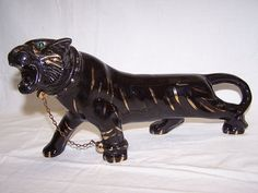 """The high gloss on this TV Ceramic Black Panther Statue portrays its magnificent sleek muscular black body. With his well detailed features and long tail curling up it is a fabulous art piece of the Black Panther Leopard. His beautiful body is  accented with Gold stripes and glass eyes. His left front foot is collared and attached to his neck collar with the original chain.This awesome TV ceramic Black Panther Cat is just like the one shown in the Archie Bunker TV show--""""All in the Family""""."""