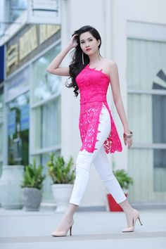 I need this Ao Dai in my life! Spring Fashion: One shoulder hot pink lace Vietnamese inspired Ao Dai top worn with fitted white crop pants.