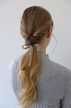 une coiffure queue de cheval inversée accessoirisée avec un ruban en velours pour apporter une touche féminine et douce à ses cheveux