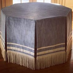 Add interest to custom table skirts and window treatments using varying widths of simple tapes. Design by Bear-Hill Interiors using tape and fringe by Samuel and Sons.