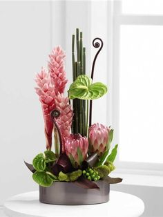 Tropical arrangement with pink ginger, green anthurium and queen protea in a silver dish
