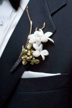 Boutonniere with stephanotis blooms with golden sprayed green berries