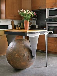 A reclaimed metal buoy is the ball under this rolling kitchen island. That someone found this buoy and had the vision to turn it into a kitchen island is amazing.