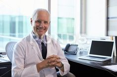 Portrait Of Doctor Wearing White Coat In Office Stock Photo