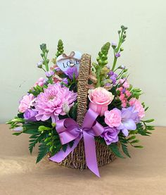 A fresh, beautiful selection of pink and lilac flowers presented in a ribbon adorned basket Basket Flower Arrangements, Creative Flower Arrangements, Funeral Flower Arrangements, Beautiful Flower Arrangements, Funeral Flowers, Floral Arrangements, Wedding Flowers, Flower Boquet, Lilac Flowers