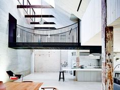 House tour: an 1880s factory in Melbourne becomes a home for two young professionals: The resultant corridor ekes out the journey and heightens the drama of release into a double-height living void that is the semblance of a mountain crevice. This interstitial space is cut through by a footbridge that connects two cliff faces — one concealing a main-suite complex, the other a study with a roof-access stair.