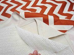 Used a fabric of canvas like thickness, a drop cloth, a rug gripper, some spray tacky glue, some scotch guard and her sewing skills to make her rug. And while I personally love the chevron pattern, this DIY can take advantage of any of your favorite patterned fabric to make your own rug.