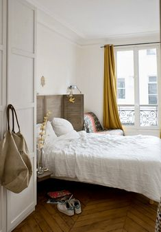 a Paris inspired chic bedroom with a shutter screen as a headboard, a herringbone floor, mustard curtains and a comfy chair Closet Bedroom, Home Bedroom, Bedrooms, Laura Lee, Parisian Bedroom Decor, Parisian Room, Diy Originales, Gold Bed, Yellow Curtains