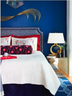 I don't usually like blue rooms, but this one is captivating. The white linens and simplified modern shapes in the art, headboard and lamp really ground the intense color.
