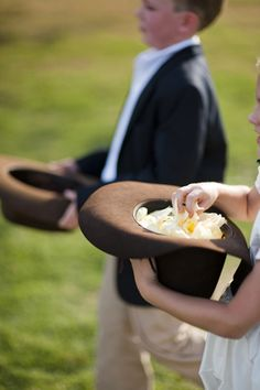 Rustic wedding ideas: use cowboy hats instead of a flower girl basket and ring bearer pillow. Or, tie the ring to a carved wooden heart and a wooden bucket with flower petals.