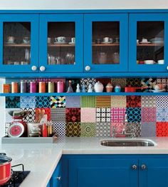 Kitchen: Blue cabinets and multi-color tile backsplash