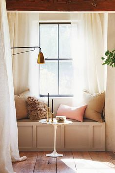Hawkins NY on domino via sfgirlbybay | beautiful light filled window nook with a build in bench | simple linen curtains and muted pastel cushions | modern brass light sconce | rustic floor boards | Update you cushion repertoire with a pale pink Bemz cushion