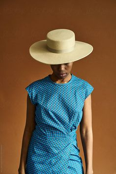 A South African woman wearing a hat and traditional Shweshwe print clothing shot against a brown background Stylist: Bielle Bellingham Photographer: Micky Wiswedal Hat: Crystal Birch Wearing A Hat, Female Portrait, African Women, Birch, Panama Hat, Stylists, Women Wear, Short Sleeve Dresses, Crystal