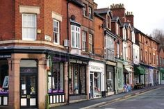 LEEK, UK - DECEMBER 31 2015: A row of small, independent shops occupies the ground floor of historic red brick terraced houses along Fountain Street in Leek, a historic market town in the Staffordshire Moorlands, England. Stock Photo - 54389894