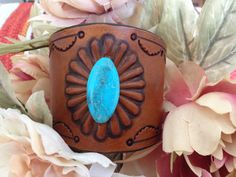 SKYSTONE SUNRISE  2 1/4 inch wide repousse stamped leather cuff with a Nacozari Turquoise bead, dyed saddle tan and lined with leather.  Fits a 6' to 7' wrist and closes with an adjustable button stud.  $85.00 www.stonesriverleather.com