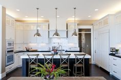 Pendant and bar stools give height...the metal draws your eye up and the black island anchors the room. great!