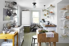 A midcentury stove, a 1950s refrigerator, an antique butcher block, and a salvaged cast-iron sink magnify this upstate New York kitchen's farmhouse charm.
