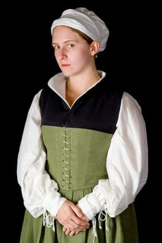 A very respectable peasants market-day best. This bodice and skirt set is made from olive linen, spiral laced front and back for ease of adjustment. Its comfortable enough to sleep in, and looks very period. This example features hand-sewn eyelets and a box-pleated skirt. It has been paired with a linen caul, apron, and chemise for a complete outfit.