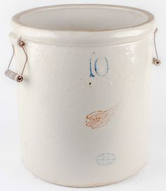 """Lot 17 in the 5.19.15 online & live auction! Antique grey color 10 gallon salt glazed crock with several markings on the front which include the red bird's wing emblem, and cobalt blue markings; """"10"""", Red Wing oval hallmark, and a patent date of Dec 21, 1915. Made in the USA by Red Wing. The jug has wire bail handles with wood grips. The crock has some surface and interior wear from age and use but no major cracks or breaks. Measures 17"""" tall with a 15.5"""" diameter. #Decor #Rustic #Home…"""