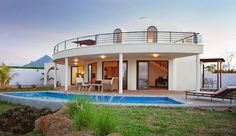 Image: Residents of the Domes of Albion enjoy stunning sunsets from the villa's huge porch, which could easily host an evening with friends. The blue swimming pool is designed to harmonize with the arc of the villa.