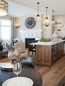 open concept or layout living room and kitchen with a large clock over the fireplace. Transitional decor