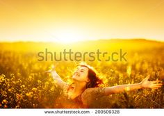 Young happy woman in canola field on sunset. - stock photo