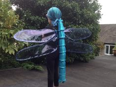 Dragonfly costume. Body: paper cups stuffed with newspaper, strung on a string and covered with iridescent material. 2 pointy bits at the tail end. Wings: garden wire covered with cellophane stapled at the edge. Wings and body roped to a piece of plastic sheeting with 6x eyelets fixed through, and sewn to a pair of braces.