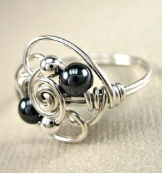 Wire wrapped ring in sterling silver and hematite in Duality design.  Introducing my new Duality ring, a design based on the number 2. Ive wrapped sterling silver wire into a tight, closed swirl and added two 3mm sterling silver beads, two 4mm hematite beads and finished with two loose, open swirls.  The ring shown is a size 7 but all sizes are available, including 1/2 and 1/4 sizes. Your ring will be custom made to the size of your choice.  ****PLEASE specify ring size when orderin...