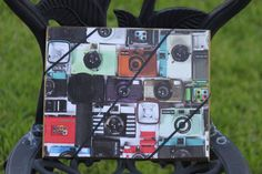 Decoupaged ribbon board with assortment of cameras