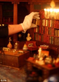 Tiny library in Queen Mary's doll house with tiny books..dailymail.uk