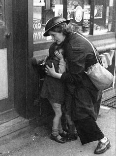 """Mrs. Mary Couchman, a 24-year-old warden of a small Kentish Village, shields three little children, among them her son, as bombs fall during an air attack on October 18, 1940. The three children were playing in the street when the siren suddenly sounded. Bombs began to fall as she ran to them and gathered the three in her arms, protecting them with her body. Complimented on her bravery, she said, """"Oh, it was nothing. Someone had to look after the children."""""""