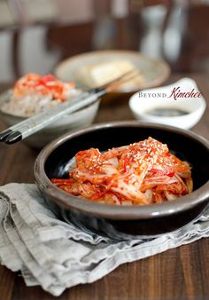 """30 minute kimchi   Beyond Kimchee 1 kg (2 lb) napa cabbage 1/2 cup Korean sea salt 5 cups water 4-5 garlic cloves 1"""" piece ginger 1 small onion diced 3 tablespoon anchovy sauce 2 teaspoon sugar 5 tablespoon Korean chili flakes 2 tablespoon Koran plum extract for tea, or 2 tablespoon apple juice with 1 teaspoon honey 2 red chilies seeded and thinly sliced, optional 2 tablespoon toasted sesame seeds"""