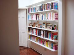 elfa solid shelving provides an elegant solution to housing a lot of books in a very little bit of space.  Notice that the shelves have been staggered to allow a bit more space for the picture frames in the middle.  Book ends on each end are an unobtrusive way to keep everything neat and tidy.