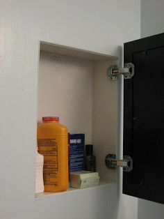 Use a framed picture and hidden hinges to hide a storage cubby recessed between the studs.