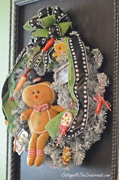 Adorable gingerbread kitchen wreath hanging on a chalkboard! Tip: Give new life to a tired & faded artificial wreath with a can of white spray paint!  | Cottage at the Crossroads